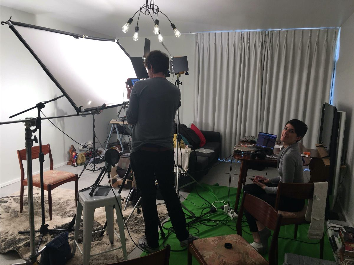 A photo of two people filming a video in a living room