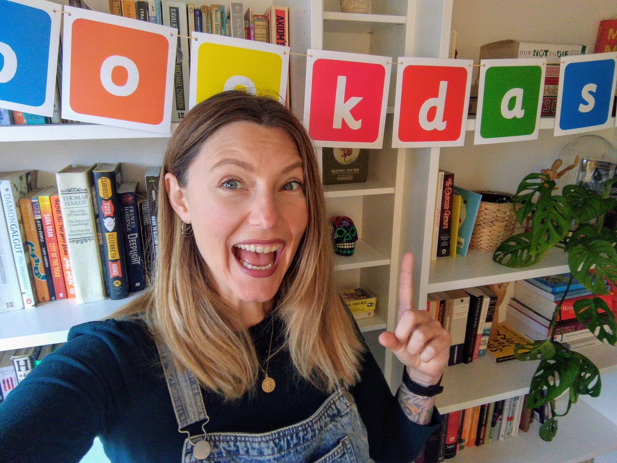 """Sam pointing at a sign that says, """"Bookdash"""""""
