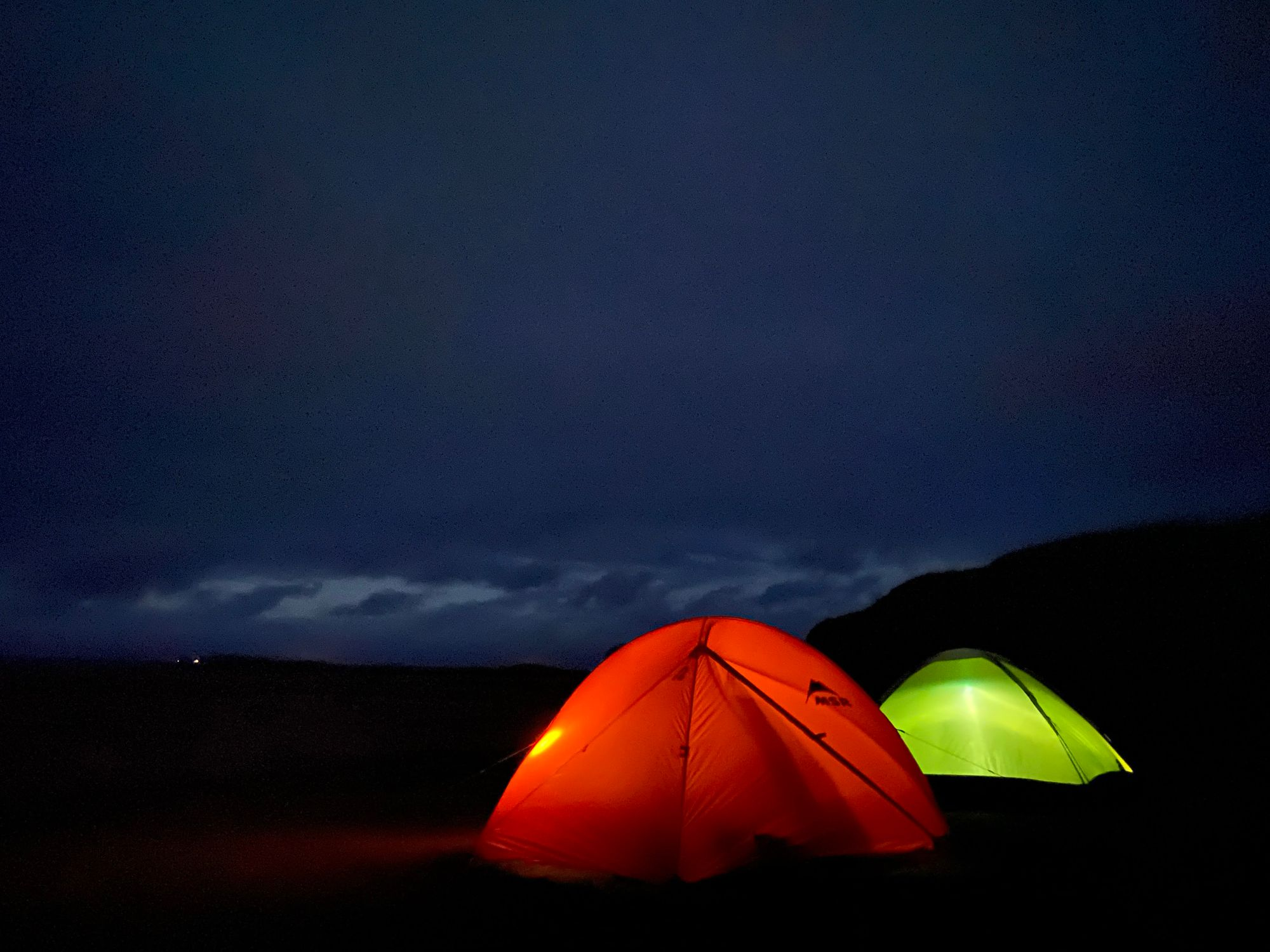 Two tents glowing in the darkness